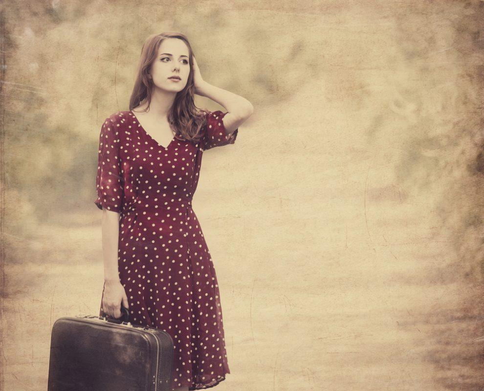 Vrouw met rode jurk en witte stippen en een oude koffer